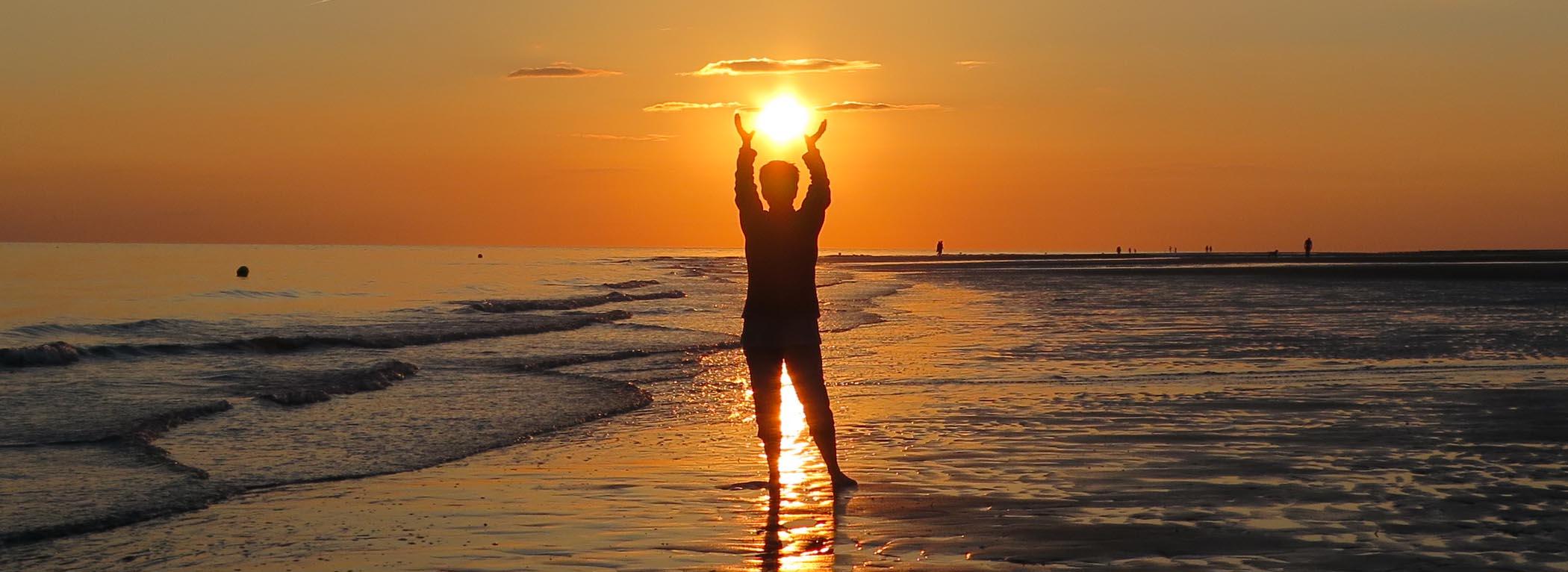 Frau hält Sonnenuntergang in den Händen